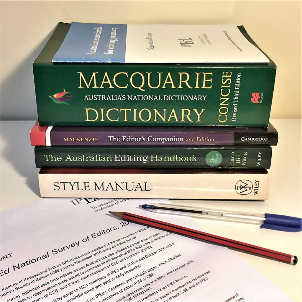 Editorial reference books and a document on a desk with pens